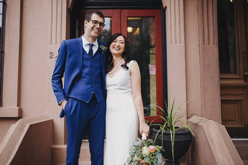 bride and groom in front of their brownstone