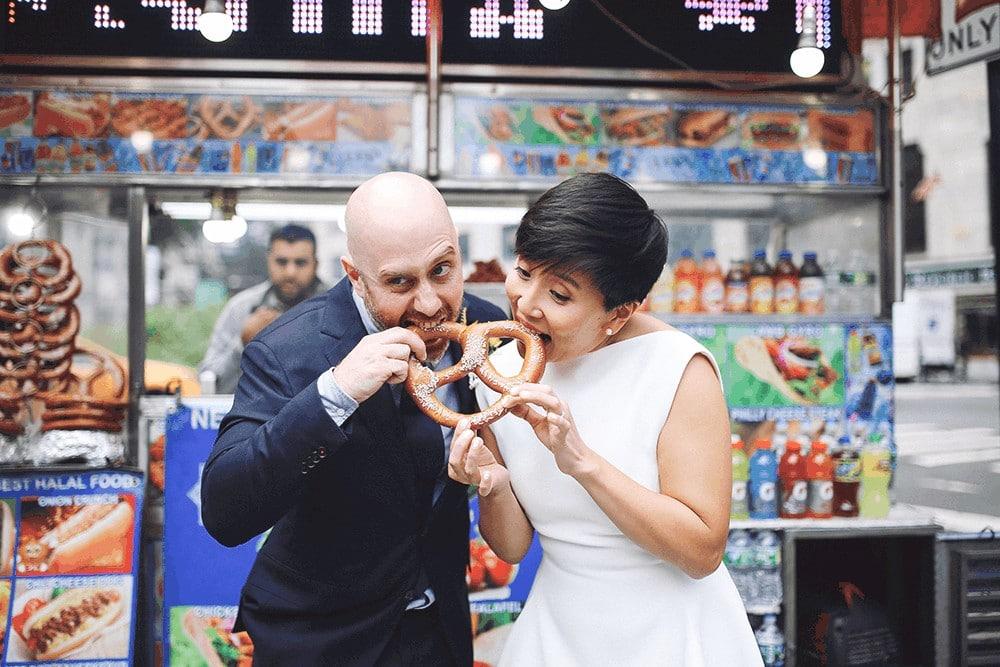 bride and groom eating new york pretzel
